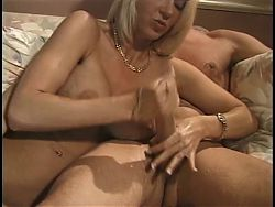 Foxy blonde with big boobs lends a sensuous helping hand to thick brown meat